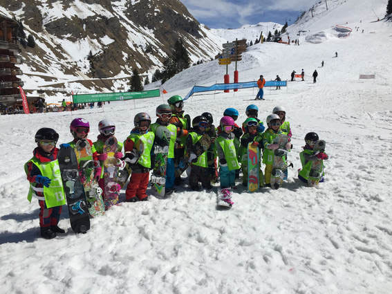 Image of a large group of kids with snowboards
