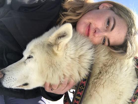 Image of a girl hugging a husky dog