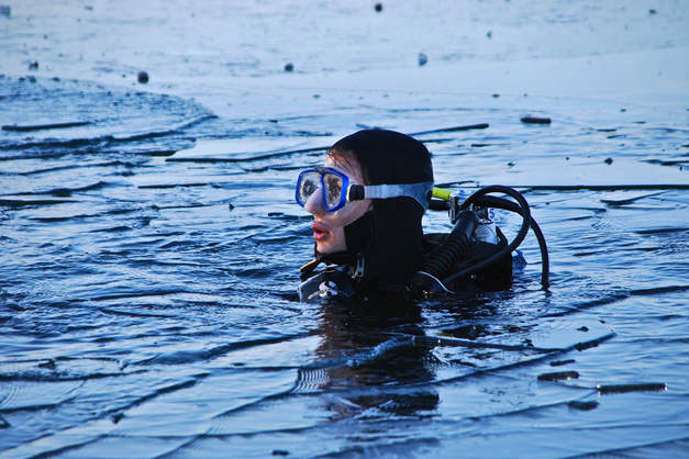 Image of an ice diver breaching the water, Morzine