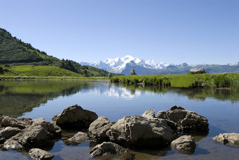 Image of an alpine lake reflecting mountains and clear sky in Morzine