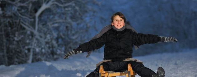 Image of a kid sledging in Winter at Morzine