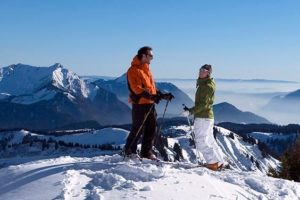 IMage of a happy skiing couple enjoying a Morzine mountaintop view